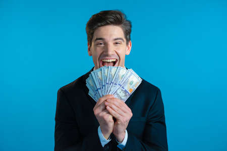 Amazed happy excited businessman with money - U.S. currency dollars banknotes on blue studio wall. Symbol of success, gain, victory.