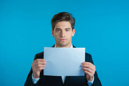 Portrait of young serious businessman in suit holding white horizontal a4 paper isolated on blue studio background.Copy space.