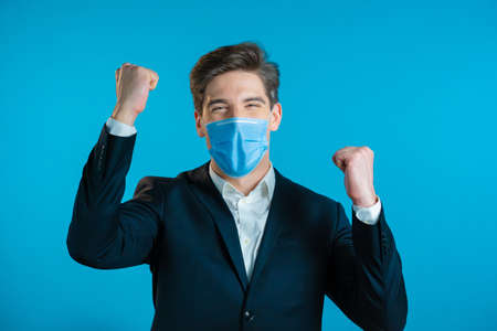 Businessman in suit and medical mask is very glad and happy, he shows yes gesture of victory, guy achieved result, goals. Surprised excited happy guy on blue background