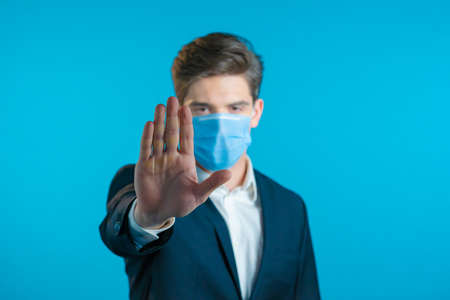Portrait of serious businessman in professional suit and medical mask showing rejecting gesture by stop palm sign. Man isolated on blue background.