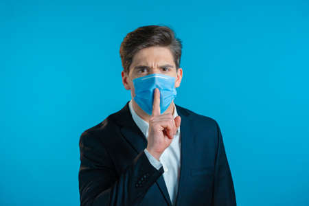 Serious business man in professional suit and mask holding finger on lips over blue background. Gesture of shhh, secret, silence. Close up.
