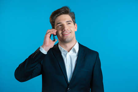 Young businessman speaks with smile on phone. Guy holding and using smart phone. Suit outfit. Blue studio background.