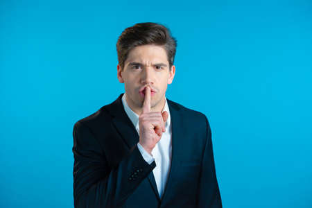 Serious business man in professional suit holding finger on lips over blue background. Gesture of shhh, secret, silence. Close up. 版權商用圖片
