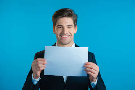 Portrait of young handsome businessman in suit holding white a4 paper isolated on blue studio background.Copy space.