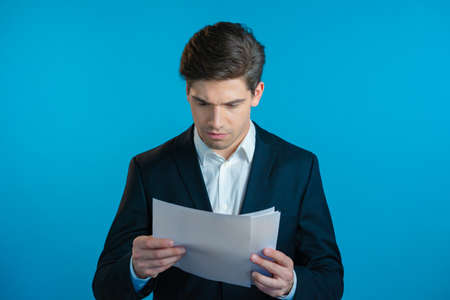 Serious businessman boss isolated on blue background studio. Young male office employee in suit jacket checking documents, reports Zdjęcie Seryjne