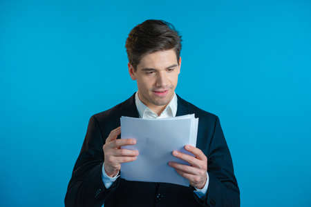 Young handsome man in suit jacket checks documents, utility bills, report. Businessman isolated on blue background. He is satisfied with work of corporate staff. Zdjęcie Seryjne