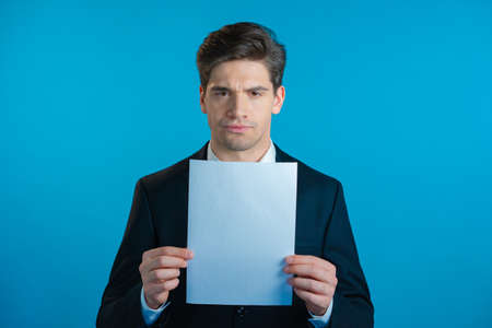 Portrait of young serious businessman in suit holding white vertical a4 paper isolated on blue studio background.Copy space.