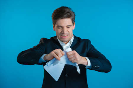 Angry businessman tearing contract in pieces. Furious male office worker throwing crumpled paper, having nervous breakdown at work, screaming in anger, stress management. Zdjęcie Seryjne