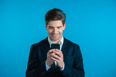 Handsome business man receives happy notification on mobile phone. Guy is beside himself with surprise and joy. He won and rejoices. Technology, success, victory, happiness concept. Zdjęcie Seryjne