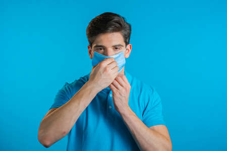 Young man puts on face medical mask during coronavirus pandemic. Portrait on blue background. Protection with respirator against COVID-19 outbreak