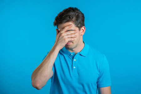 Portrait of young man doing facepalm gesture, like no, I forgot. Unhappy guy feeling sorrow, regret, drama, failure. He isolated on blue wall