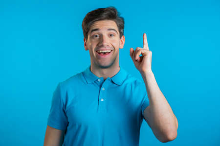 Smiling happy guy showing eureka gesture. Portrait of young man having idea moment pointing finger up on blue studio background.