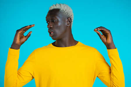 African american bored man showing bla-bla-bla gesture with hands and rolling eyes isolated on blue background. Empty promises, blah concept. Lier