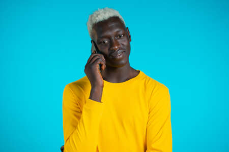 Young african american man speaks with smile on phone. Guy holding and using smart phone. Blue studio background. Foto de archivo