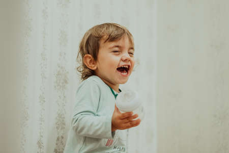 Adorable baby boy sincerely smiling, laughs contagiously. Cute toddler portrait at home.
