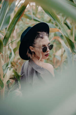 Trendy woman in plaid blazer and hipster hat at corn background. Fashion girl portrait with black sunglasses posing on natural landscape.