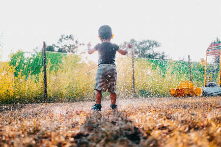 Happy adorable toddler boy having fun under rain. Baby laughs, he is very glad weather. Zdjęcie Seryjne