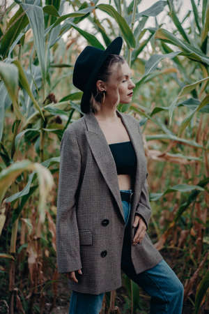 Trendy woman in plaid blazer and hipster hat at corn background. Fashion girl portrait, she posing on natural landscape.