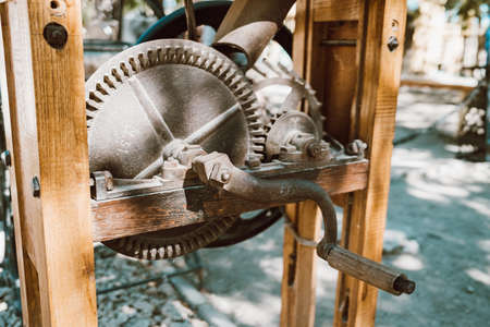 Well lifting mechanism close-up. Gate raising gear at medieval fortress. Rusty wheel and cog of manual antique machinery. Zdjęcie Seryjne