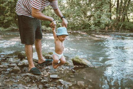 Dad holds his little baby over the river. Funny son tied his legs and does not want to swim in water. Zdjęcie Seryjne
