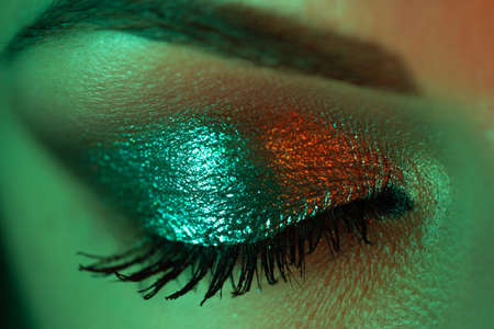 Extreme close up of female eye iris under neon light. Woman with beautiful makeup, glitter shadows and false lashes. Girls green eye. Nightlife, night club concept. Zdjęcie Seryjne
