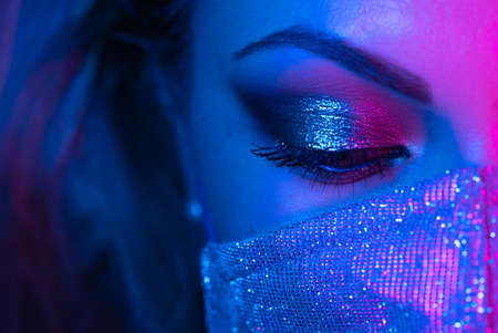 Close up of face in glitter protective mask, amazing make-up. Eye under neon light. Female with shining shadows and false lashes. Nightlife, night club, pandemic, covid-19 concept.