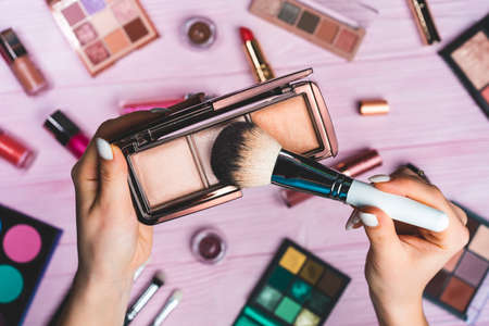 Woman working with face contouring palette - powder, bronzer and highlighter on pink flat lay cosmetics collection background. Tools in beauty industry - lipsticks, eyeshadows, glosses.