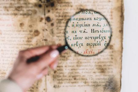 Woman researcher explores antique book with magnifier. Scientific translation of literature. Investigating manuscript with ancient writings Archivio Fotografico