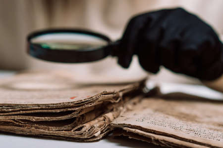 Historian scientist in gloves reading antique book with magnifying glass. Translation of religious literature. Manuscript with ancient writings. Treasures of the past. Museum piece.