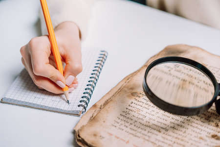 Researcher examines antique book with magnifying glass. Scientific translation of ancient literature. Studying manuscript with ancient writings