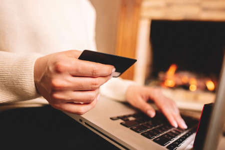 Unrecognizable woman holding credit card and using laptop computer while online shopping. Businesswoman working from home. Internet banking, money transfers concept. Foto de archivo