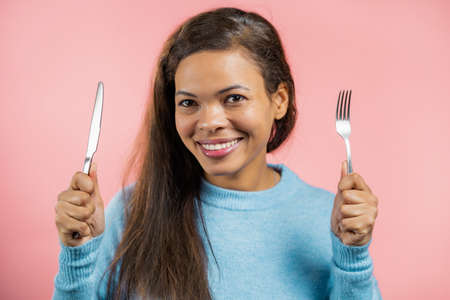 Portrait of hungry woman with fork and knife. Mature lady waiting for serving dinner dishes with cutlery on pink studio background. Standard-Bild