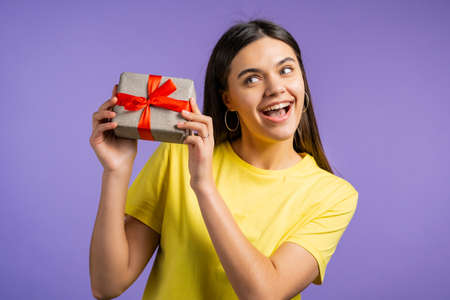 Beautiful woman received gift box with bow. She is happy and flattered by attention. Girl smiling with present on violet background. Studio portrait