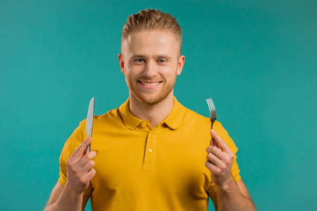 Portrait of hungry man with fork and knife. Guy waiting for serving dinner dishes with cutlery on blue studio background.
