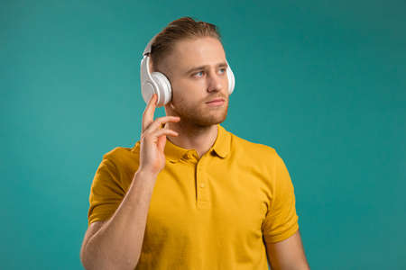 Handsome young man listening to music with wireless headphones, guy having fun, smiling in studio on blue background. Dance, radio concept.