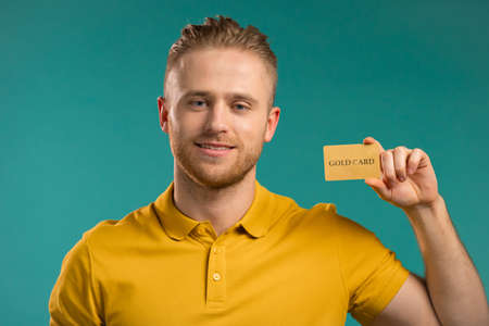 Successful man look to camera and showing unlimited gold credit card on blue background. Stockfoto