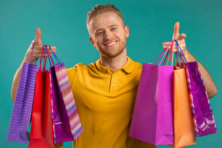 Handsome man holds shopping paper bags on blue studio background. Guy bought presents on sales with discounts. Stockfoto