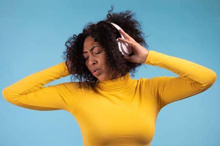 African woman dancing with wireless headphones isolated on blue studio wall. Cute lady in yellow wear, she is singing. Music, radio, happiness, freedom, youth concept.