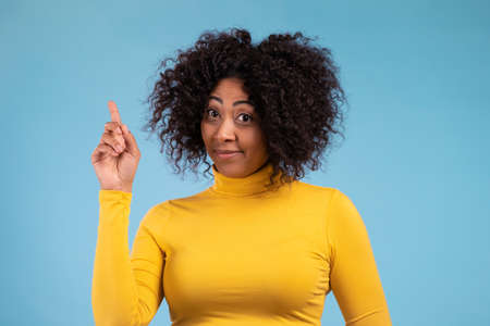 Portrait of african thinking pondering woman having idea moment pointing finger up on blue studio background. Smiling happy girl showing eureka gesture.