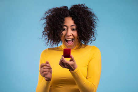 Lady screaming, jumping , she is happy to get present, proposition for marriage. Attractive african woman holding small jewelry box with proposal diamond ring on blue wall background. Stockfoto