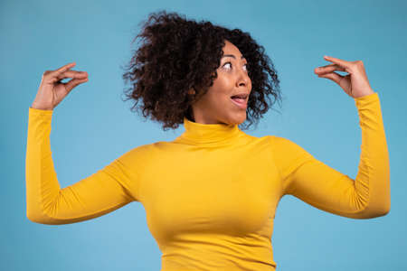 Pretty african woman showing bla-bla-bla gesture with hands isolated on blue background. Empty promises, blah concept. Lier.