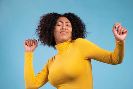 Mixed race woman with afro hairstyle dancing positive on blue studio background. Pretty female model in yellow wear. Party, happiness, freedom, youth concept.