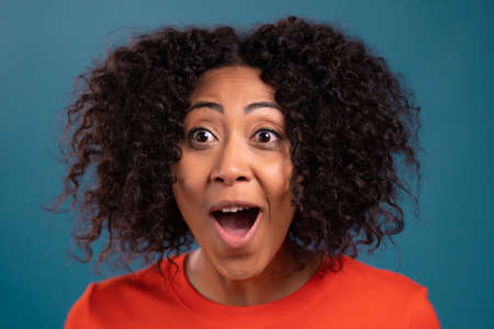 African woman is very glad, she screaming WOW loud. Concept of sales, profitable offer. Excited happy lady on blue studio background.