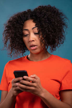 Attractive african woman using mobile phone on blue background. Technology, success, victory, happiness concept.