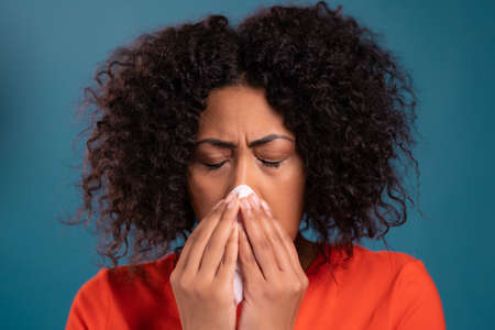African woman sneezes into tissue. Isolated girl on blue studio background. Lady is sick, has a cold or allergic reaction. Coronavirus, epidemic 2021, illness concept