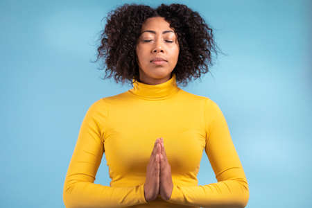 Calm african woman praying with hands together symbolizing prayer and gratitude. Mudra. Yoga concept. Blue light studio background.