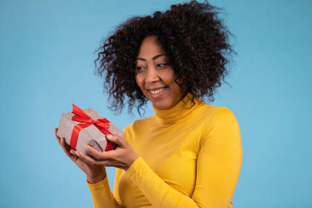 Excited african woman received gift box with bow. She is happy and flattered by attention. Girl smiling with present on blue background. Studio portrait Stockfoto