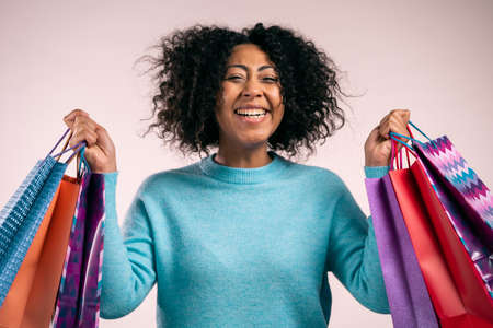 Happy african woman with colorful paper bags after shopping on beige studio background. Concept of seasonal sale, purchases, spending money on gifts