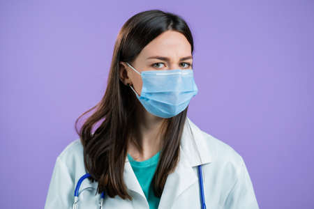 Portrait of nurse in protective medical mask and coat disapproving with no head gesture. Denying, Rejecting, Disagree, Portrait of female doctor on violet background