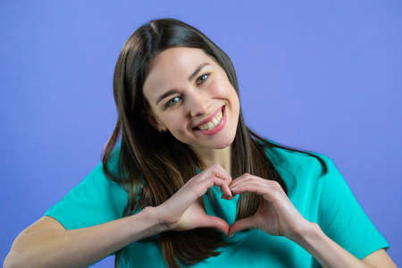 Kind pretty woman making sign of shape heart near her chest. Violet background. Women health, volunteering, donation help and love concept.